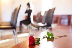 Rode rozen en vrouw die bij begrafenis in kerk schreeuwen royalty-vrije stock foto's