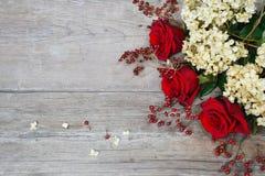 Rode rozen, hydrangea hortensia, heupen op houten achtergrond stock foto's