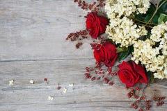 Rode rozen, hydrangea hortensia, heupen op houten achtergrond royalty-vrije stock fotografie