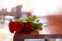 Rode rozen op bank bij begrafenis in kerk stock afbeelding