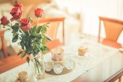 Rode rozen op lijstbovenkant in uitstekende stijl en kleuren Stock Foto
