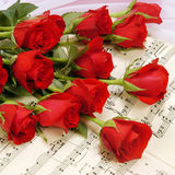 Rode rozen op muziekscore Stock Fotografie