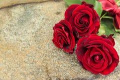 Rode rozen op steenlijst Royalty-vrije Stock Afbeeldingen