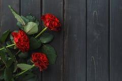 Rode rozenbloemen over zwarte houten achtergrond stock fotografie