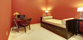Rode ruimte met bankbed en bureau. Stock Fotografie