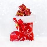 Rode santa` s kous met giften in sneeuw, Kerstmiskaart Stock Afbeelding