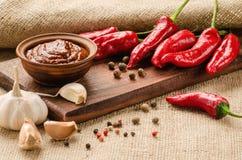 Rode saus, kruiden en peper op een keukenraad Stock Afbeelding
