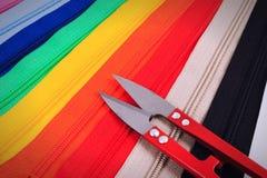 Rode schaar op kleurrijke ritssluitingen in verschillende kleuren Stock Foto's