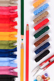 Rode schaar, potlood en knopen op kleurrijke ritssluitingen in verschillende kleuren Stock Afbeeldingen