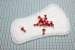 Rode scherpe bureauspelden en menstruatie katoenen sanitaire dagelijkse stootkussens op de plaiddeken Foto voor de bescherming va Royalty-vrije Stock Afbeelding