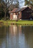 Rode schuur in de herfst die in vreedzame vijver wordt weerspiegeld Royalty-vrije Stock Fotografie