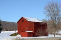 Rode schuur in de winter bij de achterlandweg Stock Fotografie