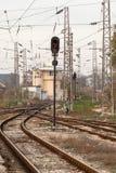 Rode seinpaal en spoorwegsporen Het verkeerslicht toont rood signaal op spoorweg Stock Foto