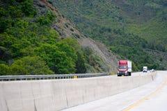 Rode semi vrachtwagen met aanhangwagen het uitgaan heuvel bij het winden van groene highw Royalty-vrije Stock Foto's