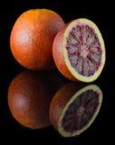 Rode sinaasappel op een zwarte achtergrond Stock Afbeelding