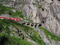 Rode sneltrein op toneel steenachtige St Gotthard spoorwegbrug en tunnel, Zwitserse Alpen, ZWITSERLAND stock afbeeldingen