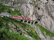 Rode sneltrein op toneel steenachtige St Gotthard spoorwegbrug en tunnel, Zwitserse Alpen, ZWITSERLAND stock fotografie