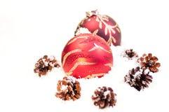 Rode snuisterijen en pinecones op sneeuw Royalty-vrije Stock Foto