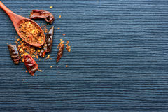 Rode Spaanse peper droge peper en houten lepel op zwart hout Stock Foto's