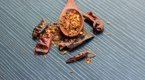 Rode Spaanse peper droge peper en houten lepel op zwart hout Royalty-vrije Stock Fotografie