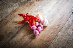 Rode Spaanse peper en rood ui en knoflook op een oude houten achtergrond Royalty-vrije Stock Foto's