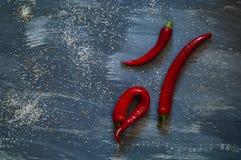 Rode Spaanse peperpeper op een donkerblauwe achtergrond met zoutwater, zoute, hoogste mening, natuurlijke lichte, vrije ruimte vo Stock Foto