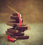 Rode Spaanse peperpeper op stapel donkere chocoladestukken Royalty-vrije Stock Afbeelding