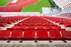 Rode stadionzetels met rode renbaan en groen gras. Royalty-vrije Stock Foto's