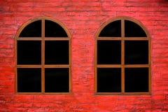 Rode steenmuur met houten vensters stock fotografie