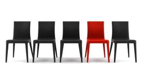 Rode stoel onder zwarte stoelen die op wit worden geïsoleerd¯ stock foto's
