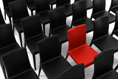 Rode stoel onder zwarte stoelen die op wit worden geïsoleerdo Stock Foto
