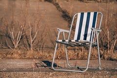 Rode stoel op oceaan zijrotsencontrasten met de stormachtige zwart-witte achtergrond royalty-vrije stock foto
