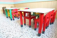 Rode stoelen en kleine lijsten in de peuterklas stock fotografie