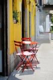 Rode stoelen tegen een gele geschilderde muur Stock Afbeeldingen