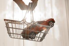 Rode stuk speelgoed auto in boodschappenwagentje stock afbeeldingen