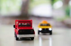 Rode stuk speelgoed autovrachtwagen en gele oude taxiauto op weg op vage bac stock foto