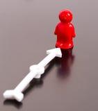 Rode stuk speelgoed mens en pijl Stock Afbeelding