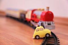 Rode stuk speelgoed trein en gele stuk speelgoed auto op spoorweg stock afbeeldingen