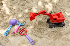 Rode stuk speelgoed vrachtwagens op zandspeelplaats Royalty-vrije Stock Afbeeldingen
