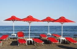 Rode sunshades op het strand Stock Afbeelding