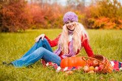 Rode sweater, jeans, lilac hoed, picknickbos Royalty-vrije Stock Foto's