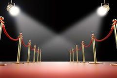 Rode tapijt en kabelbarrière met glanzende schijnwerpers Stock Foto's