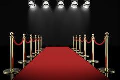 Rode tapijt en kabelbarrière met glanzende schijnwerpers Stock Fotografie