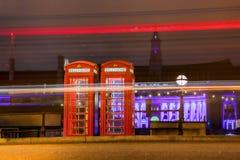 Rode TELEFOONCELLEN bij nacht in Londen, Engeland Stock Afbeeldingen