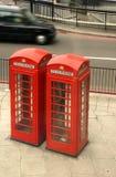 Rode telefooncellen en zwarte taxi Stock Afbeeldingen