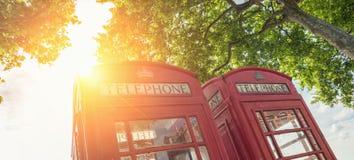 Rode telefoondozen bij een de zomerdag in Londen, het Verenigd Koninkrijk Stock Fotografie