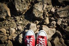 Rode tennisschoen op barst droge grond stock afbeeldingen