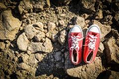 Rode tennisschoen op barst droge grond stock foto's