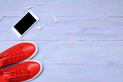 Rode tennisschoenen en smartphone met hoofdtelefoons royalty-vrije stock fotografie
