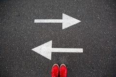 Rode tennisschoenen op de asfaltweg met getrokken pijlen die aan twee richtingen richten royalty-vrije stock foto's